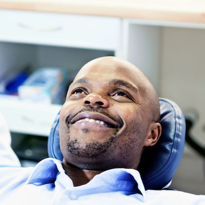 A man smiling in a dental chair because his knows his oral health is protected with our exceptional family dentistry