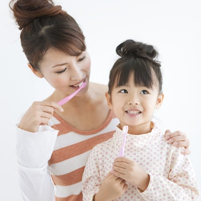 A young mother and daughter brushing their teeth to show we offer sealants and dental hygiene as part of our family dentistry in Edgewater NJ
