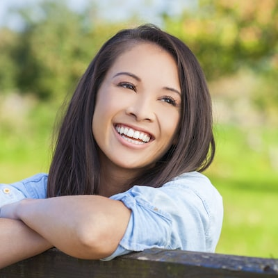 Woman with white smiling standing outside and leaning on a fence smiling thanks to laser dentistry which is offered as part of our family dentistry in Edgewater NJ