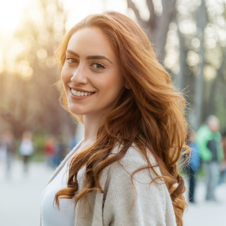 Woman with fiery hair smiling in an urban setting thanks to porcelain veneers which is one of our cosmetic dentistry options in Edgewater
