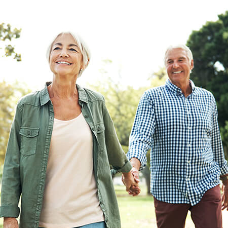 A senior man and woman smiling and walking to illustrate that this New Jersey dentist offers Restorative Dentistry