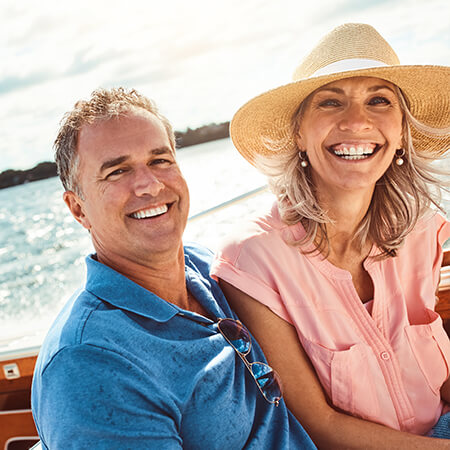 Older couple smiling on boat with the woman wearing a straw hat