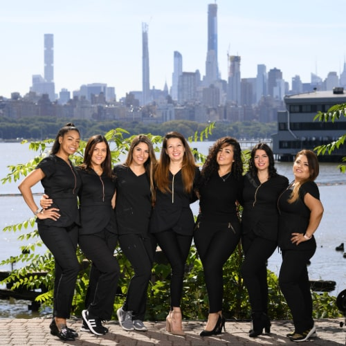 Our Edgewater, New Jersey team members smiling outside our dental practice overlooking the Hudson River